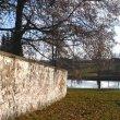 Zeď kolem harrachovské hrobky s výhledem na rybník.
